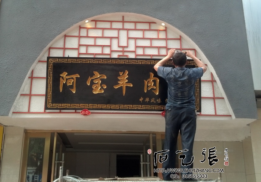 这是我们给十堰市一家名为《阿宝羊肉面》店面制作的仿古刻字牌匾。使用了实木整块木板子,长2.2米,宽0.7米,厚0.06米,字体选用电脑行楷体,四周雕刻富贵不断图,纯手工刻制,以黑色打底,金色描金,对比分明。